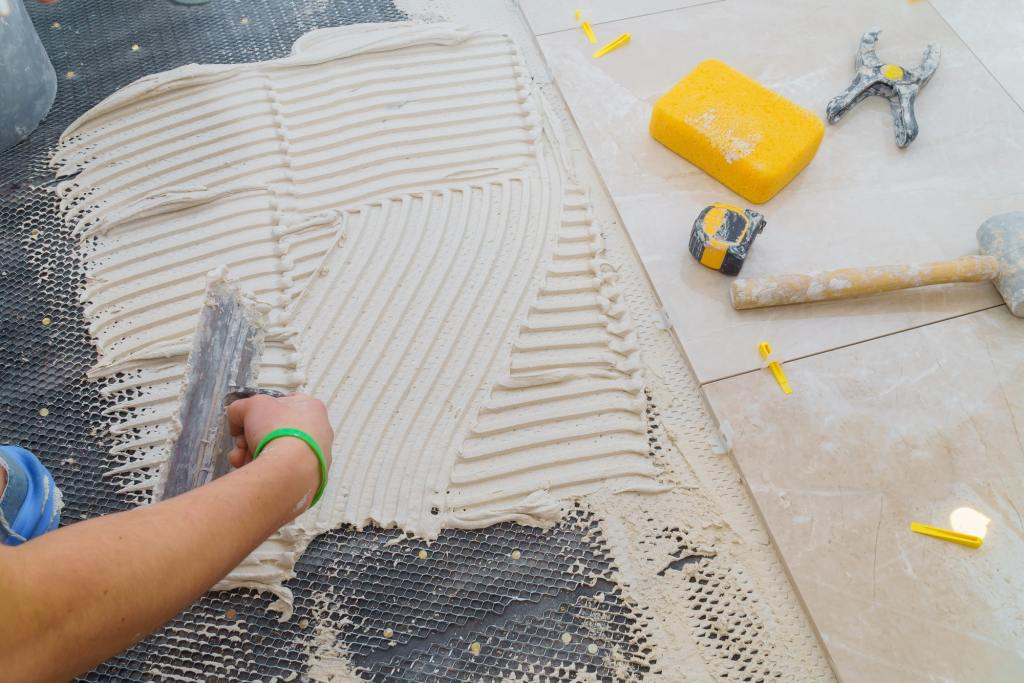 Floor tiles installation. Ceramic tiles and tools for home improvement, renovation