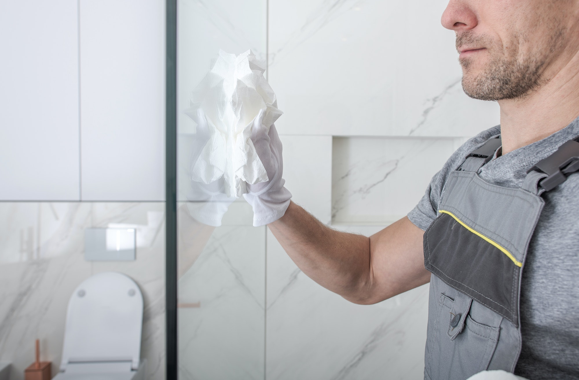 Man Cleaning Shower Glass In Bathroom.