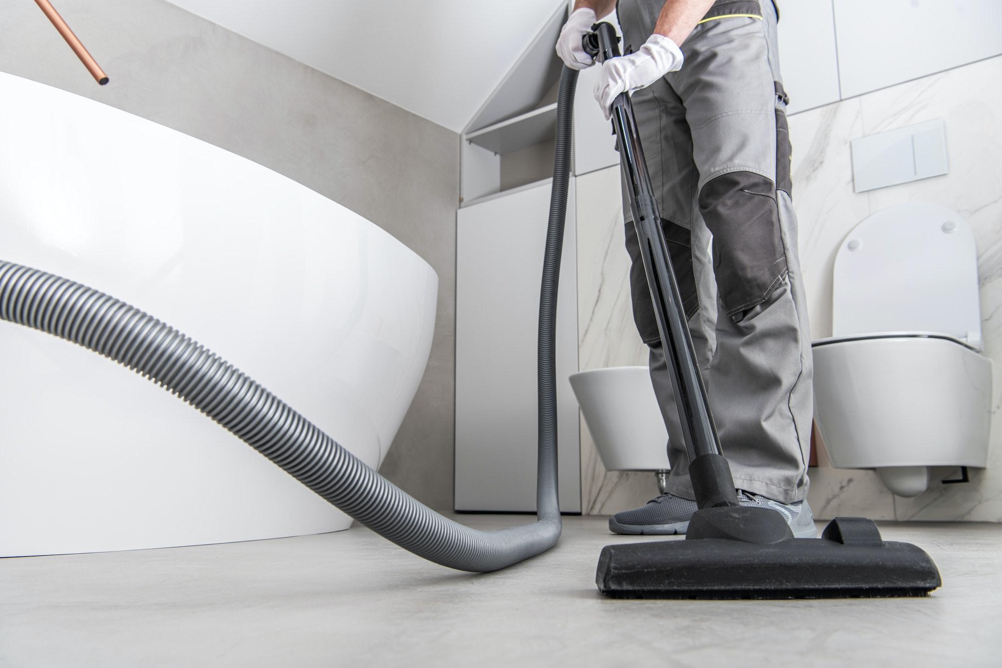 Man Vacuuming White Tile Floor In Bathroom.