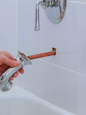 Plumber working in shower faucet with thermostat